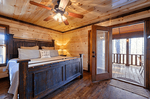 cabin bedroom with views of pine trees